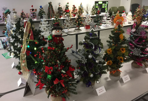 Room full of decorated tabletop holiday trees