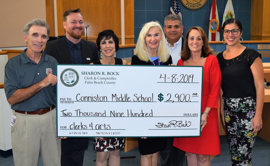Representatives of the Clerk's office and Conniston Middle School hold a jumbo check for $2,900