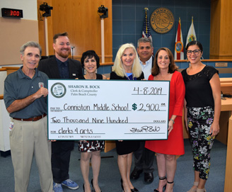 Representatives of the Clerk's office and Conniston Middle School hold a jumbo check for $2,90