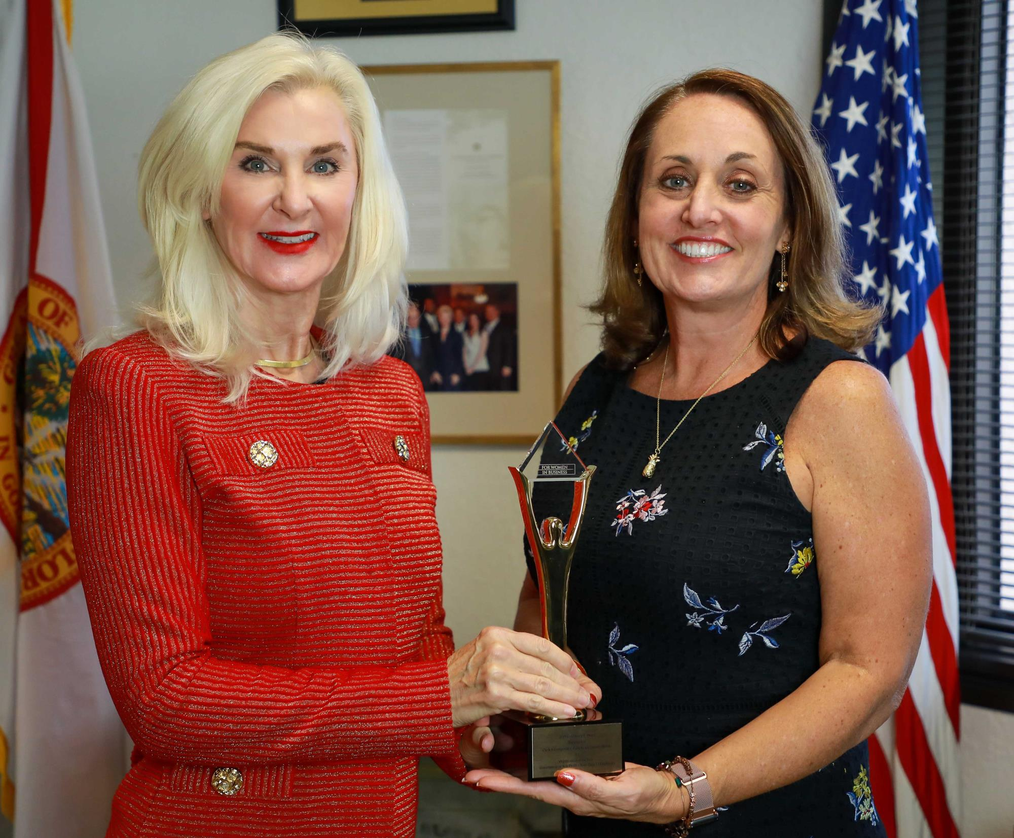 Clerk Sharon R. Bock and Chief Operating Officer Shannon R. Chessman holding Stevie Award trophy